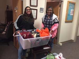WGRC Intern, Anam, presents packed purses for Aid to Inmate Mothers