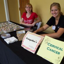 Volunteers smile from behind a table featuring chocolate covered strawberries from Evangeline's and information about cervical cancer