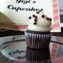 A chocolate cupcake with white cream, topped with chocolate chips, from Gigi's Cupcakes