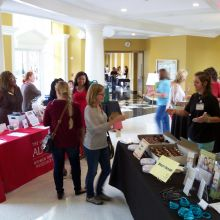 A volunteer and guest interact at the4 Angel Cakes/ body image table