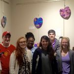 A group of 8 students stand in front of a wall featuring painted and decorated wooden hearts