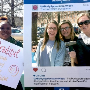 WGRC student assistants and an intern pose with an instagram photo frame and poster
