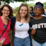 Three students pose with teal ribbons and candles as they wait at Take Back the Night