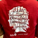 """Back of a Red T-shirt that has """"IDEAL: Intentionally Diversifying Engagement and Leadership"""" written in the silhouette of a woman's head"""