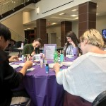 3 students and a staff therapist paint canvas tiles around a purple table