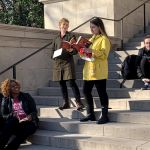 Two students perform on the steps of Gorgas library as other performers standby.