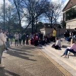 A crowd gathers and looks on as performers stand on the steps of Gorgas Library