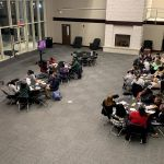 Students are seated at 6 round tables in the Great Hall at the Ferguson Center with two screens positioned at the front of the room displaying questions