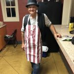 A man poses in a kitchen wearing an Alabama apron