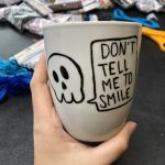"""A hand holds a mug with the words """"Don't tell me to smile"""""""