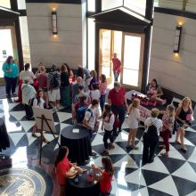 Aerial view of guest gathered near ticket and takeout box tables in the Shelby Hall Rotunda