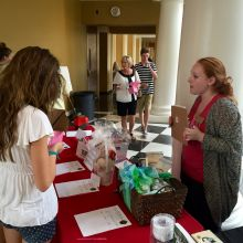 A guest and volunteer speak at the silent auction table