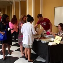 Guests visit a table featuring chocolate goodies and information on healthy relationships