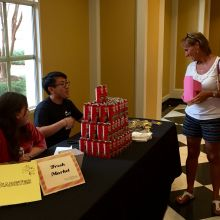 Guests speak with volunteers at a table featuring chocolate milk, sponsored by The Fresh Market