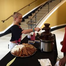 Guest dips marshmallow in chocolate fountain